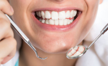 Closeup of woman holding dental tools while showing healthy white teeth